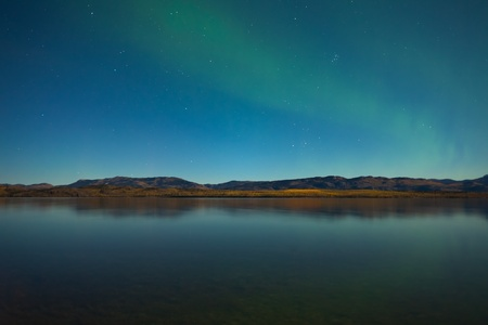 whitehorse: Northern lights (Aurora borealis) in moonlit night over Lake Laberge, Yukon, Canada, in fall.