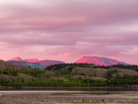 Distant mountains glowing in sunset light at Lake Laberge, Yukon Territory, Canada. photo