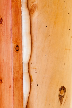 Polyurethane foam seals gap in wooden frame construction conserving energy.