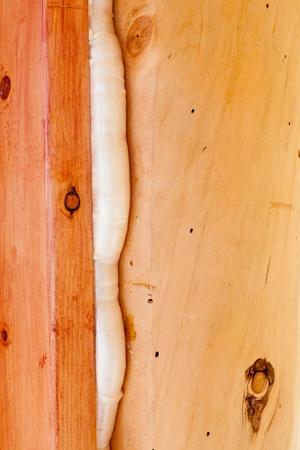 Polyurethane foam seals gap in wooden frame construction conserving energy. photo