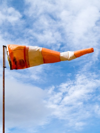 Red and white windsock wind filled partially clouded blue sky background photo