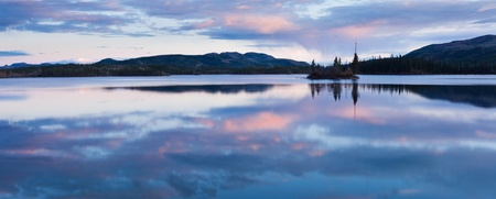 Calm lake reflecting sky at sunset, Twin Lakes, Yukon Territory, Canada. photo