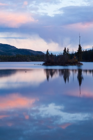 Calm lake reflecting sky at sunset, Twin Lakes, Yukon Territory, Canada.