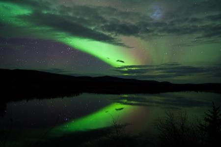 Night Sky Stars, clouds and Northern Lights mirrored on calm lake in Yukon, Territory, Canada. Stock Photo