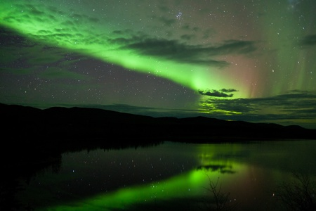 borealis: Night Sky Stars, clouds and Northern Lights mirrored on calm lake in Yukon, Territory, Canada. Stock Photo