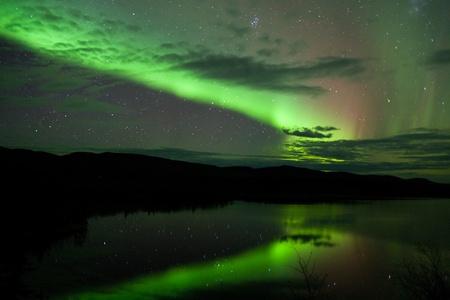 Night Sky Stars, Wolken und Northern Lights gespiegelt am ruhigen See in Yukon, Territory, Kanada.
