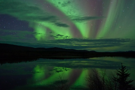 Night Sky Stars, clouds and Northern Lights mirrored on calm lake in Yukon, Territory, Canada. Banque d'images