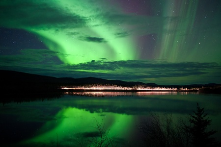 yukon: Night Sky Stars, clouds and Northern Lights over country road at lake shore, Yukon, Territory, Canada.