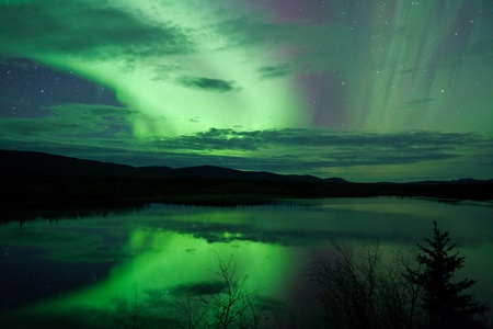 the aurora: Night Sky Stars, clouds and Northern Lights mirrored on calm lake in Yukon, Territory, Canada. Stock Photo