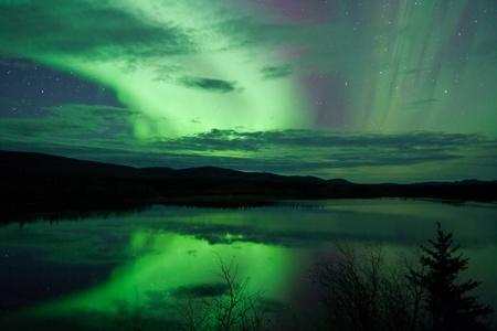Night Sky Sterne, Wolken und Northern Lights gespiegelt am ruhigen See in Yukon, Territory, Kanada.