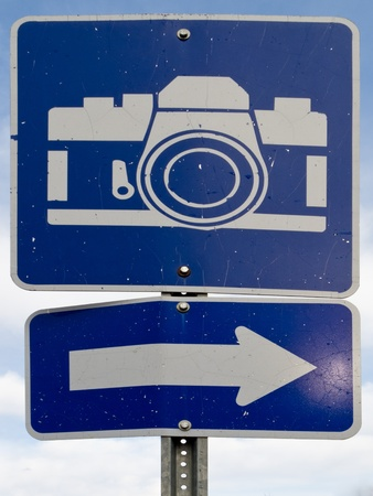 Point-of-interest blue road sign with white camera icon and directional arrow. photo
