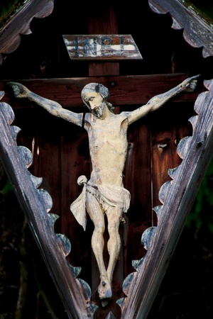 An old and weathered representation of the body of Christ hanging on the cross during the Crucifixion mounted outside