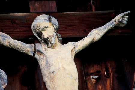 Closeup view of the face of a weathered old figure of Jesus Christ nailed to the cross outdoors Banco de Imagens