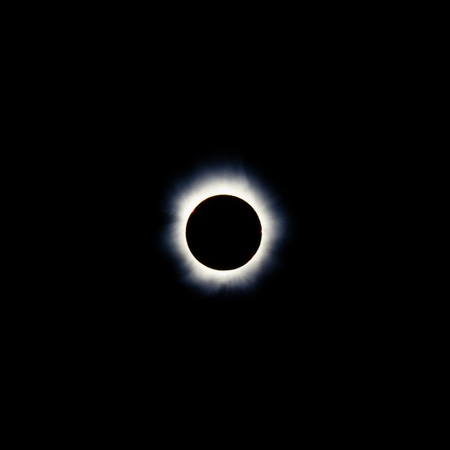 Total solar eclipse with the moon obscuring the disc of the sun so that only the corona is visible as a bright ring photo