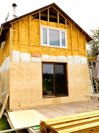 Renovation of old house, wall is sprayed with liquid insulating foam before the siding goes on  Redactioneel