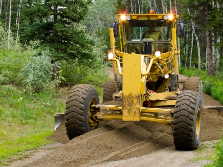 Large yellow grader resurfacing a narrow rural road through a poplar forest with fresh gravel Stock Photo