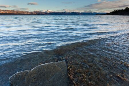Fall snow on distant mountain range on east shore of Lake Laberge, Yukon Territory, Canada photo