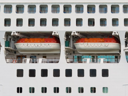 lifeboats: Lifeboats surrounded by portholes stowed in recesses hanging from davits on a the side of large cruiseliner Stock Photo