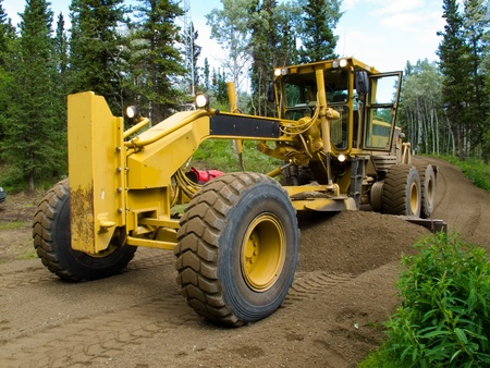 grader: Large yellow grader resurfacing a narrow rural road through a forest with fresh gravel