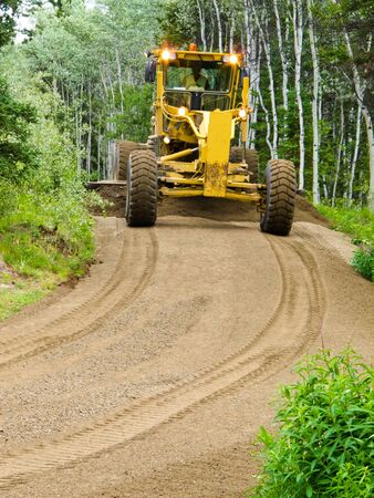 grading: Large yellow grader resurfacing a narrow rural road through a poplar forest with fresh gravel Stock Photo