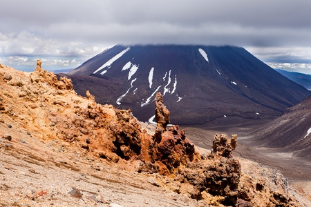 tongariro national park: Bizarre lava sculptures in front of active volcano cone of Mount Ngauruhoe as seen from Mount Tongariro in Tongariro National Park, North Island of New Zealand Stock Photo