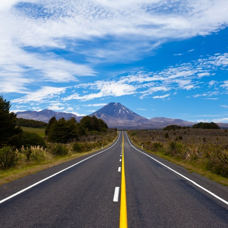 Straight highway leading to active volcano cone of Mount Ngauruhoe in Tongariro National Park, North Island of New Zealand photo