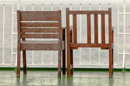 slats: Two old wooden chairs standing abandoned on balcony next to each other