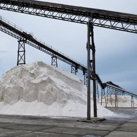 sodium: Stockpile of sea salt crystals under conveyor belt in a saline refinery plant