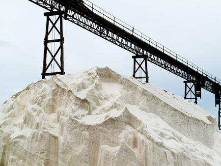 Stockpile of sea salt crystals under conveyor belt in a saline refinery plant