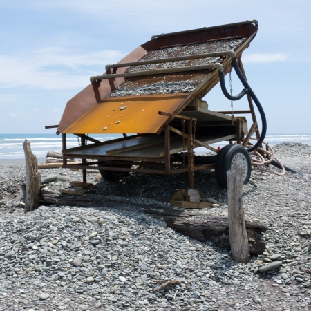 yielding: Metal sluice box on placer mining claim for extracting alluvial gold dust from gravel beach of West Coast of New Zealand South Island