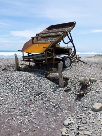 placer: Metal sluice box on placer mining claim for extracting alluvial gold dust from gravel beach of West Coast of New Zealand South Island