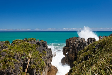 orificio nasal: Surf Mar de Tasman choque en las rocas panqueque en Punakaiki, Isla Sur, Nueva Zelanda, llevando agua salada salpique fuera de respiraderos de alta en el cielo azul.