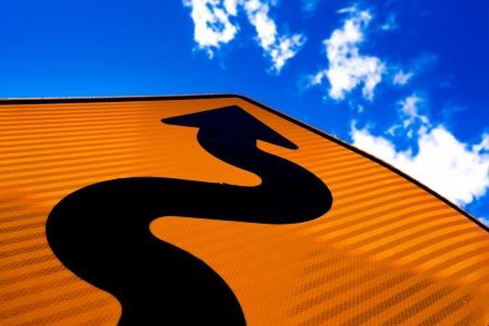 Wavy arrow on road sign pointing upward into a cloudy blue sky in a concept of achievement, advancement and success photo