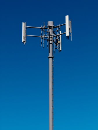 Metal tower with antennas for mobile cell phone telecommunications against blue sky with copyspace photo