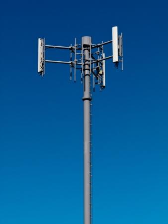 Metalen toren met antennes voor mobiele telecommunicatie mobiele telefoon tegen de blauwe hemel met copyspace Stockfoto