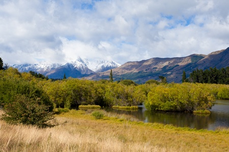 Wetland swamp in glacial Rees Dart river valley near Glenorchy with Mt Aspiring National Park, Southern Alps, vista backdrop forming an iconic New Zealand landscape photo