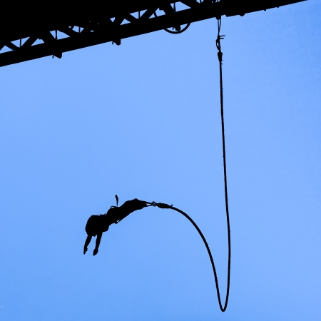 Silhouette of bungee jumper against blue sky
