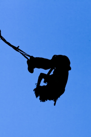Silhouette of bungee jumper against blue sky photo