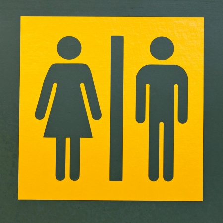 differentiation: Signpost for men and women or male and female as often used to indicate restrooms with two silhouetted figures standing side by side on yellow