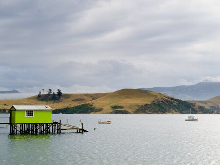 Otago peninsula coastal landscape scenery with green boat shed in sheltered water, Otago, South Island near Dunedin, New Zealand photo