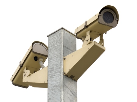 Twp pole mounted security video cameras facing in opposite directions for maximum surveillance coverage isolated on white background photo