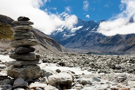 hooker: Rock cairn in Hooker Valley on a trail leading to Aoraki, Mount Cook, highest peak of Southern Alps, an icon of New Zealand partially covered in clouds