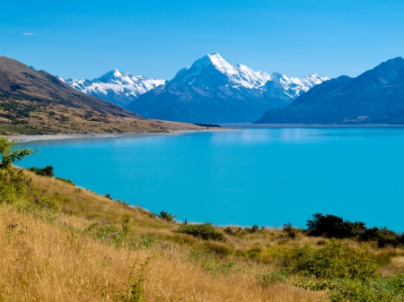Mighty Aoraki Mount Cook towering over glacial Lake Pukaki in hues of turquoise from silt, Aoraki Mount Cook National Park, Canterbury, South Island, New Zealand photo