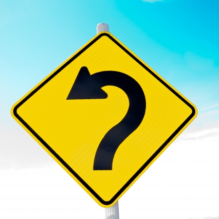 alerts: Sharply curving arrow on road sign pointing left in a concept of turning around, correction and betterment