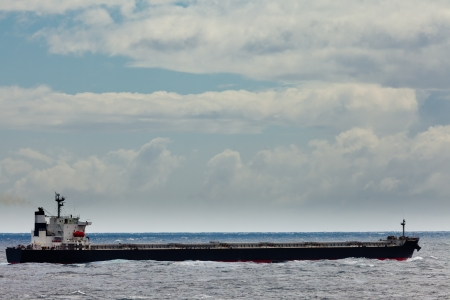 shipload: Loaded oil tanker, long and low in the water, on the ocean sea under stormy sky clouds