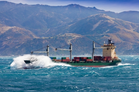 Loaded container freighter ship sailing in stormy ocean with tall and heavy breakers still near shore Stockfoto