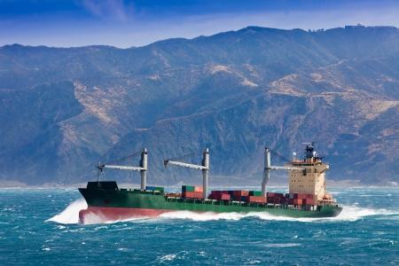 Beladen container vrachtschip schip dat in stormachtige oceaan met hoge en zware branding nog steeds vlak voor de kust