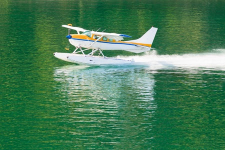 hydroplane: Small propeller float-plane or hydroplane takes off across flat calm water of lake Stock Photo