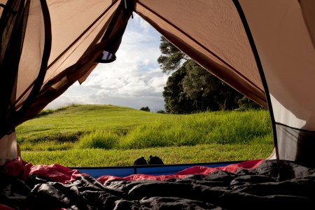 Campsite nature view of lush green countryside from inside a tent with sleeping bags laid out on the floor Stock Photo