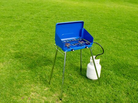 gas stove: Small blue two flame propane gas cook stove barbecue with a gas tank bottle attached standing alone on a green lawn